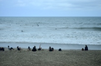 Gals exercising on the sand, surfers in the water.