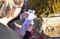Angelika reading the Geocache log we found at the graveyard